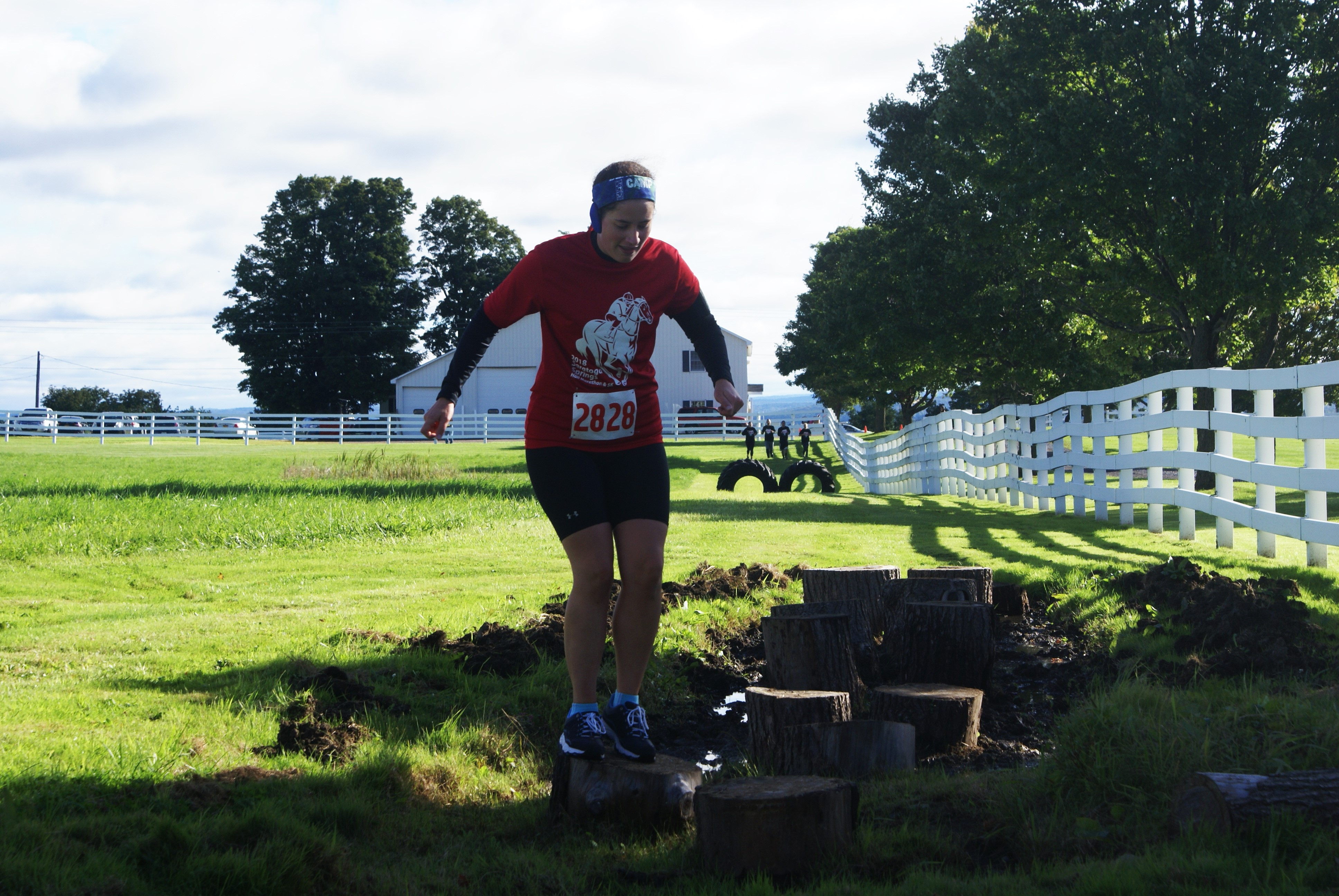 A participant of the Udderly Rugged Run at Maple Ridge Center hops from stump to stump in a muddy pit.